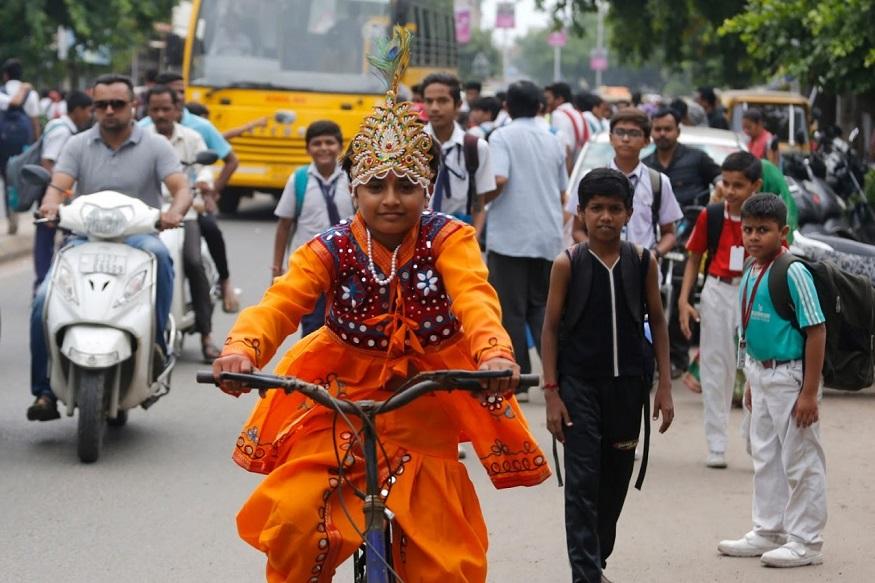 जम्मू - पर्यावरणाचं रक्षण करत सायकलवर शाळेत जात असताना श्रीकृष्णाच्या वेशातला विद्यार्थी.