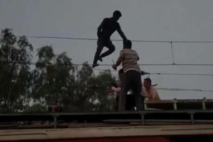 वीजेच्या तारेवर चढलेल्या तरुणाला वाचवण्यासाठी आली ट्रेन, VIDEO VIRAL