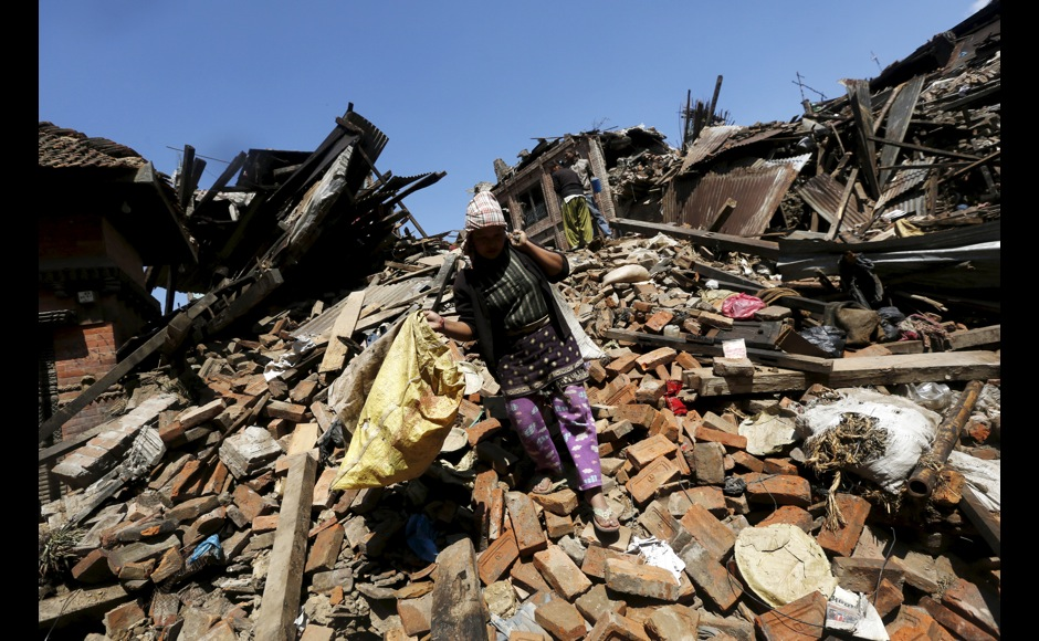 A woman carries belongings as she walks over collapsed house after earthquake in Bhaktapur